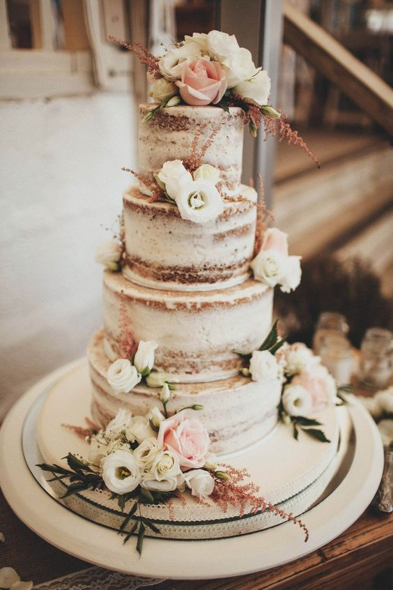 semi naked wedding cake with neutral florals looks rustic