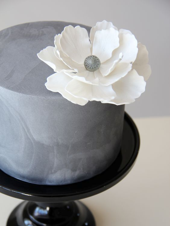 textural concrete wedding cake with a large white flower
