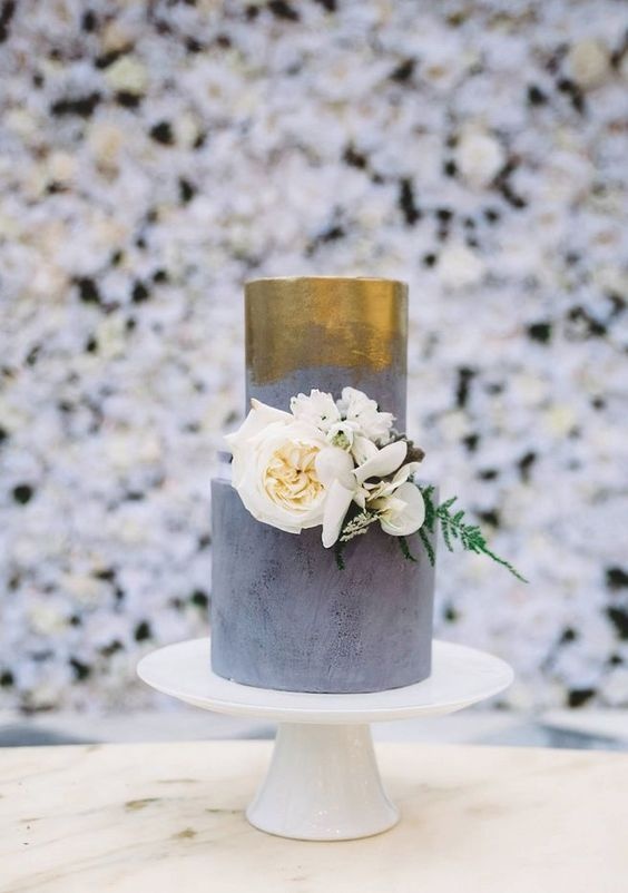 concrete and gold metallic wedding cake decorated with white flowers