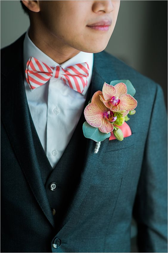 a dark suit with a vest, a white shirt, a striped bow tie and a bold boutonniere