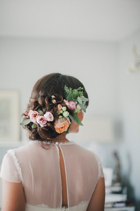 beautiful curly updo with pastel flowers and greenery tucked in