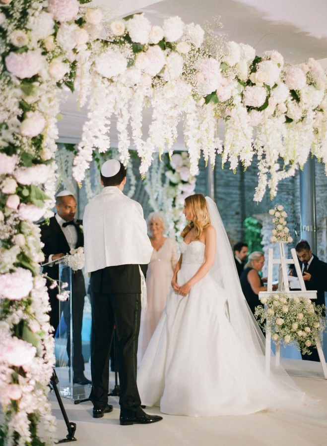 A lush wedding arch decorated with white and blush flowers for the ceremony
