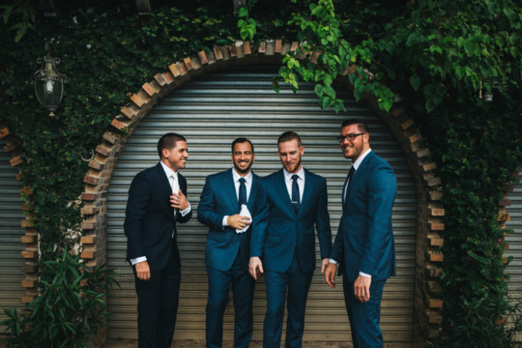 The groom was wearing a black suit with a white shirt and tie, the groomsmen rocked blue suits with ties and ocher shoes