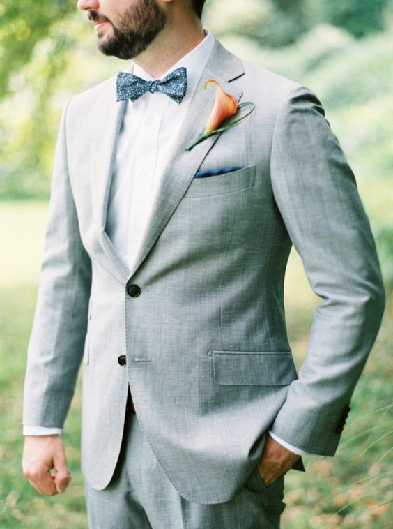 a light grey suit with a white shirt and a patterned bow tie