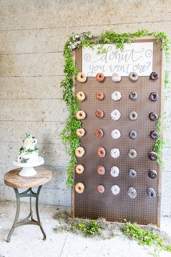 a simple pegboard with hooks decorated with greenery as a donut bar