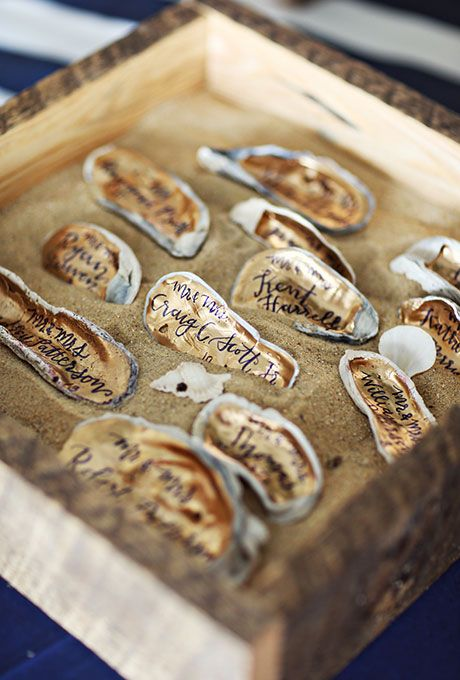 gold-painted oyster shell escort cards for a beach wedding