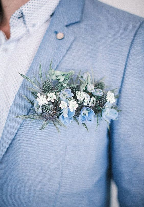 light blue groom's suit, a patterned shirt and a thistle and blue flower boutonniere
