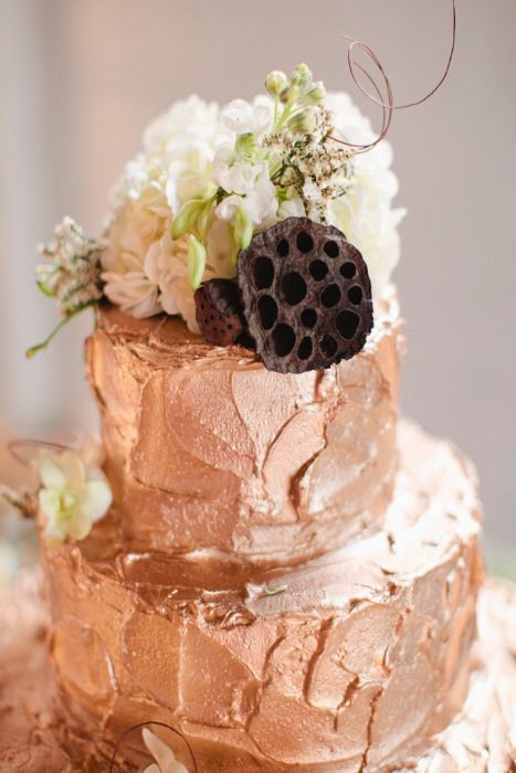 rough frosting copper wedding cake with flowers and a lotus