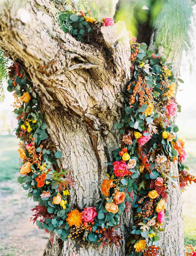 I love the idea of decorating the tree with floral garlands and using it as a natural backdrop