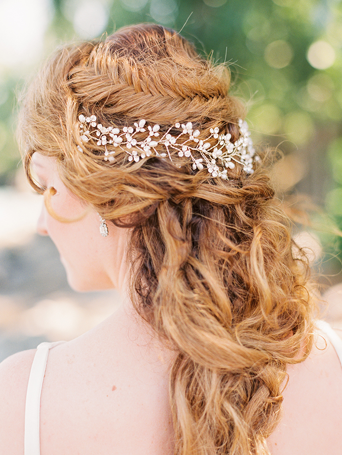 The bride was wearing a boho braided half updo with a jeweled headpiece