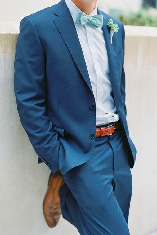 a blue suit, a light blue shirt, a mint bow tie and ocher shoes