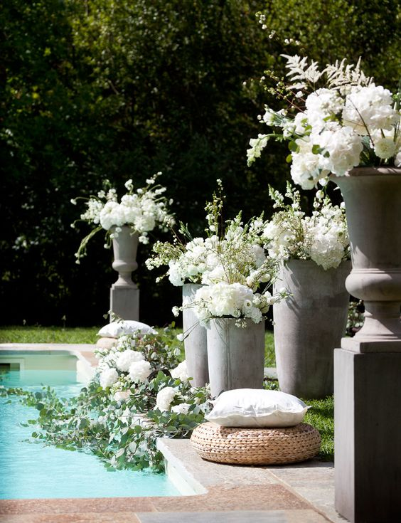 lush white florals and greenery on the side of the pool and right in it