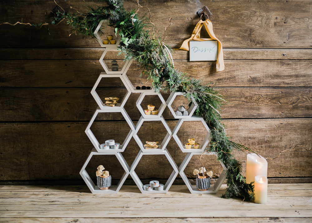 Unique dessert display in honeycomb shapes decorated with greenery