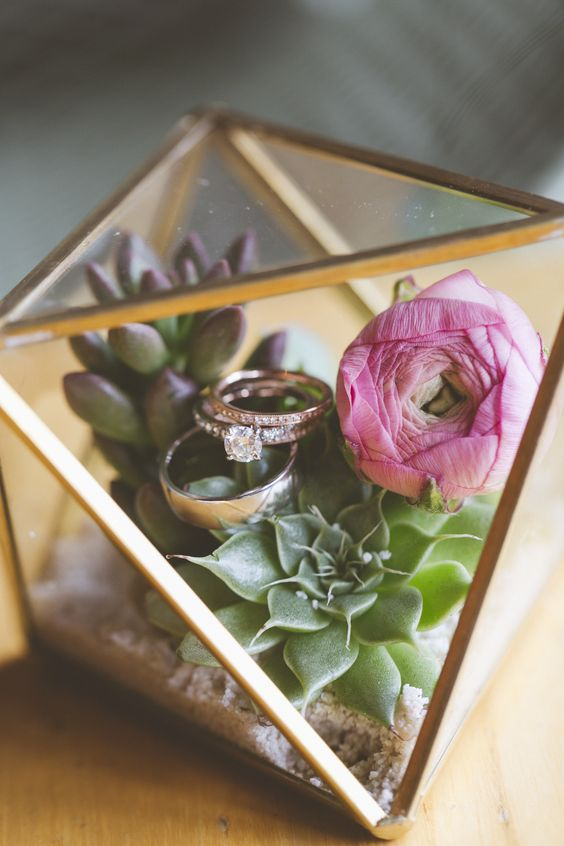 a terrarium filled with succulents and flowers as a ring box