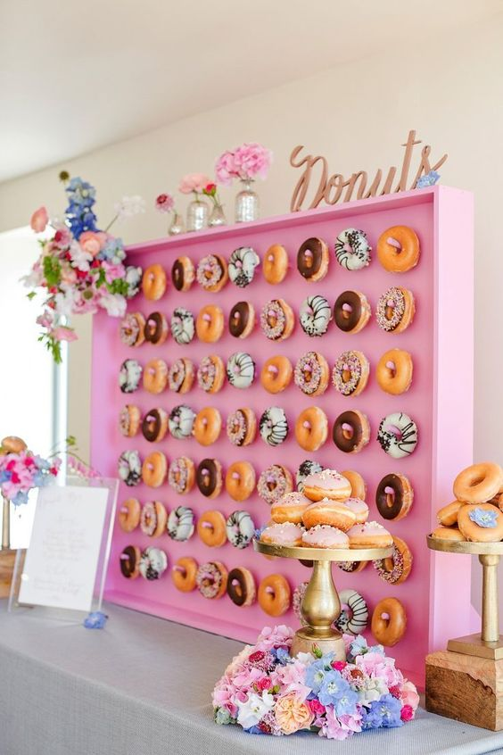 glam pink donut bar with hooks for comfortable display, lots of flowers