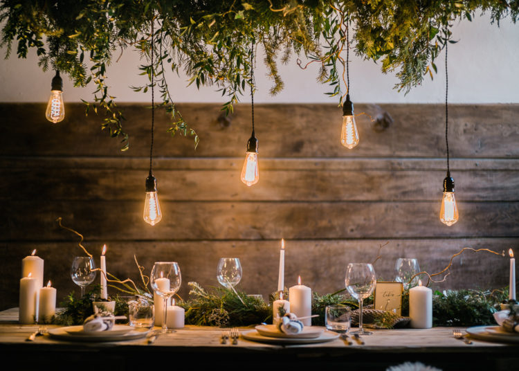 The tablescape lit with edison bulbs, decorated with greenery and candles
