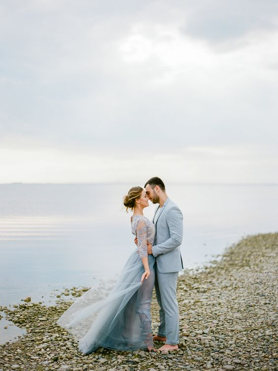light blue groom's suit and a flowy light blue wedding dress with sleeves for a sea-loving couple