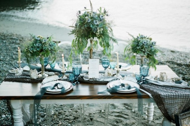 The wedding tablescape was done in blue and grey, with fishing net, blue glasses and greenery centerpieces on stands