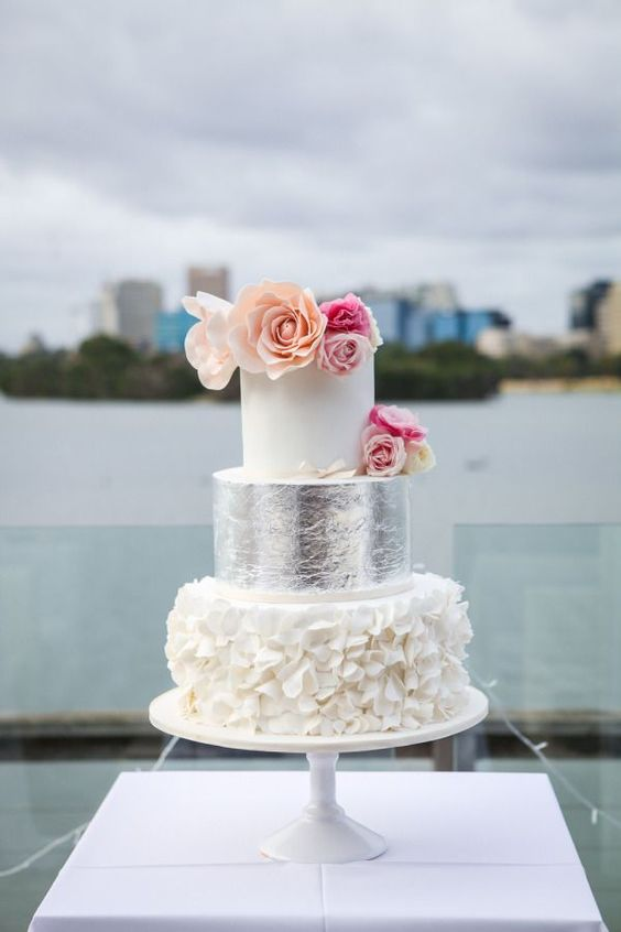 a white cake with a ruffled and a silver tier, bold flowers on top