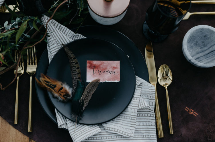 The place setting was decorated with watercolor cards, feathers and black plates