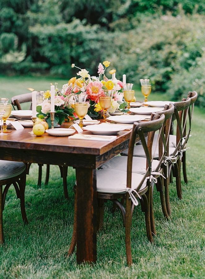 The table was laid with the same bold flowers, colorful glasses, candles and even fruit for decor