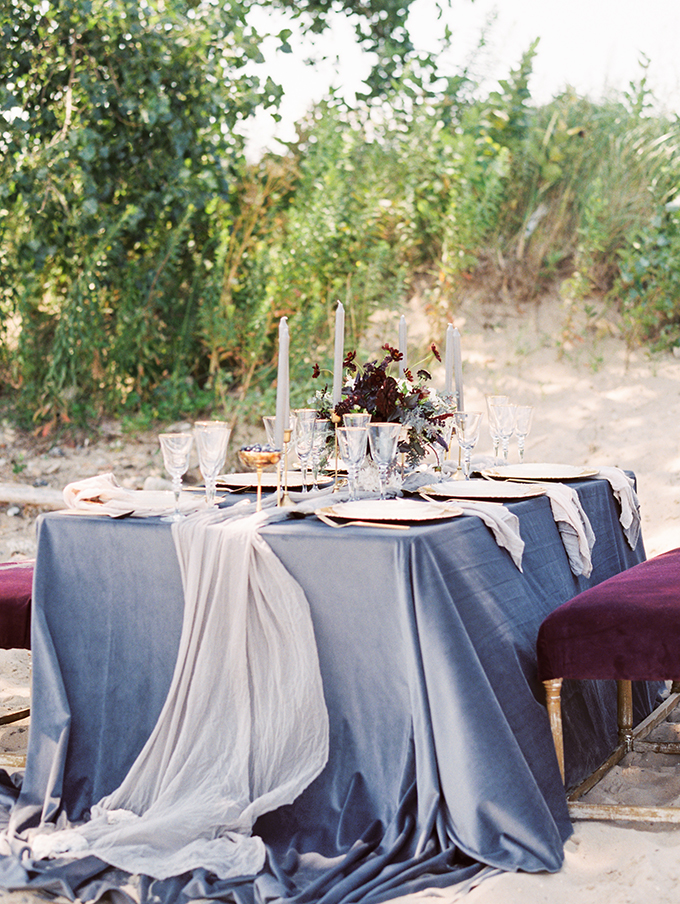 The tablescape was decorated in blue and blush, with gold rim glasses, tableware and dark flowers