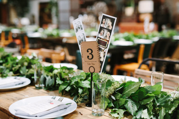 Greenery garlands were used instead of centerpieces, and photos of the couple for table numbers