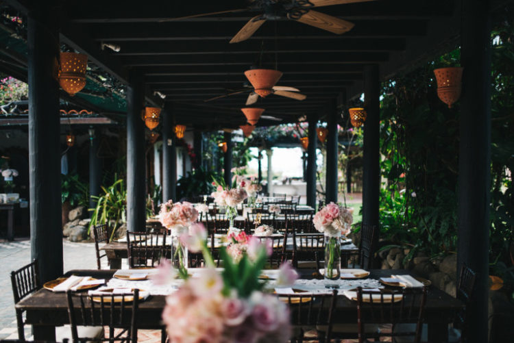 Simple outdoor reception with blush florals and fans over all the tables for more comfort