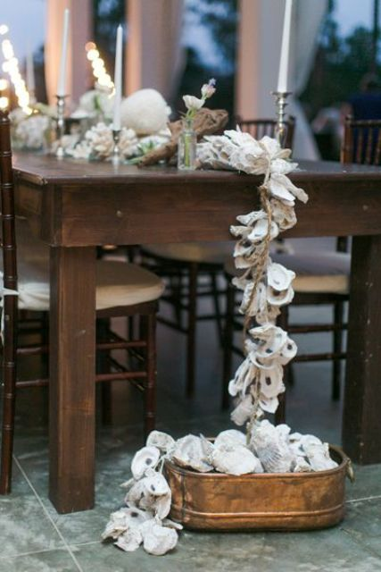 an oyster garland in a metal bath, driftwood and candles