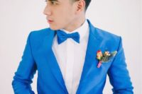 11 neon blue suit and a bow tie, a white shirt, a colorful boutonniere