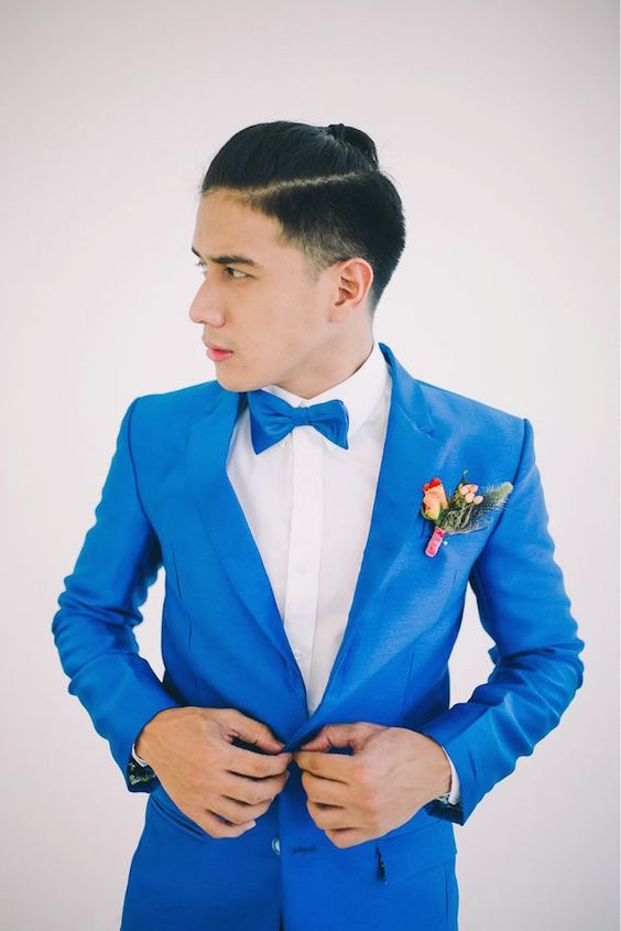 neon blue suit and a bow tie, a white shirt, a colorful boutonniere