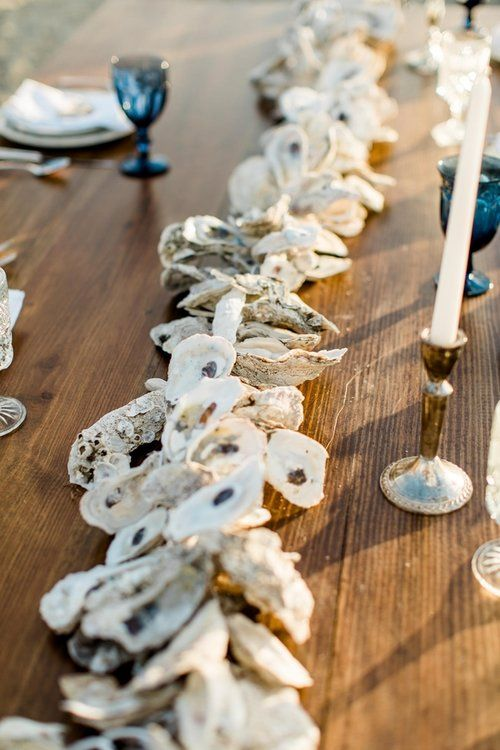 an oyster shell garland, candles and blue glasses are right what you need for an island wedding