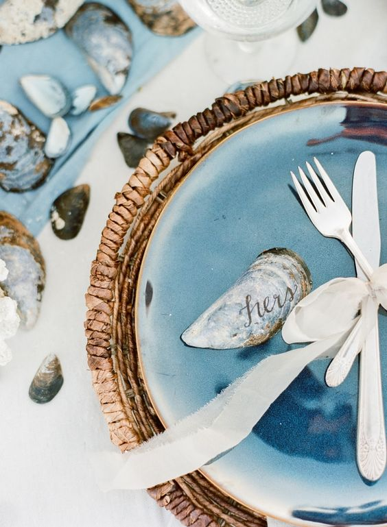 coastal wedding tablescape with a bold blue plate, a wicker platter and shells