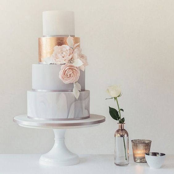 marble and white wedding cake with a copper tier and flowers