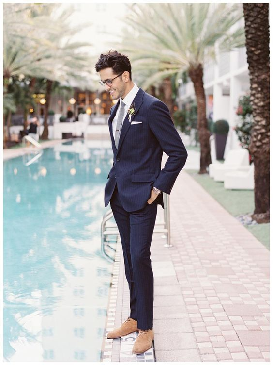 navy thin striped suit with a white shirt and a grey tie, ocher shoes and glasses