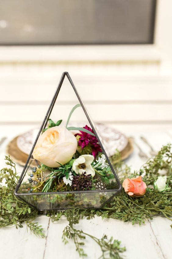 simple metal terrarium with greenery and flowers inside