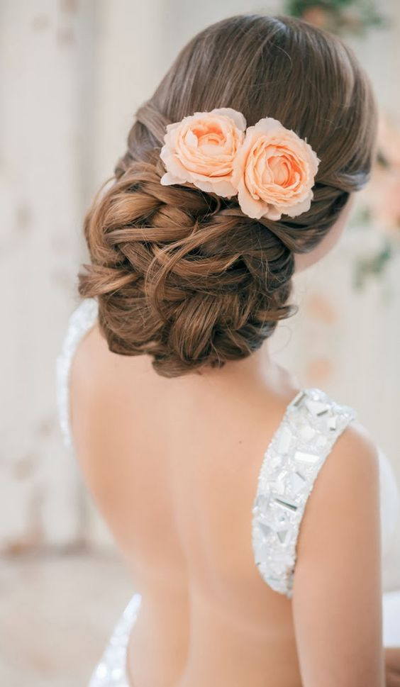 elegant twisted and curly wedidng updo with peach-colored blooms
