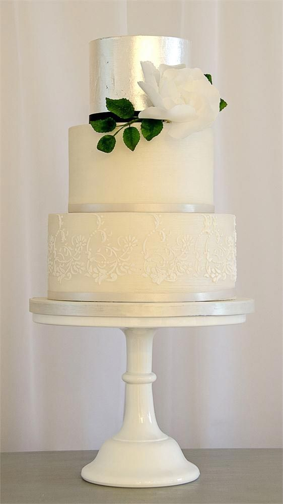 ivory lace wedding cake with a top metallic tier and a white rose