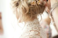 16 messy wedding updo with small neutral flowers