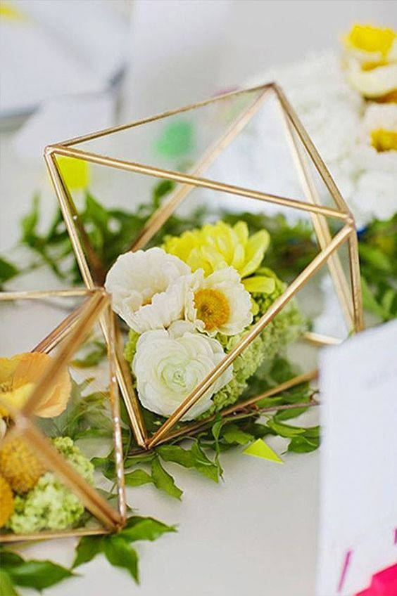 copper terrariums with various flowers inside