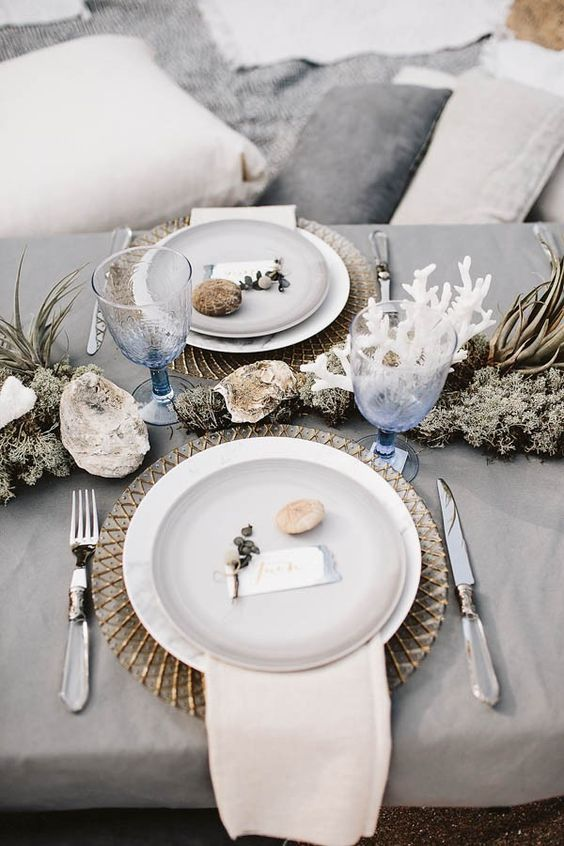 grey tablescape with stones, air plants, corals and blue glasses inspired by the ocean