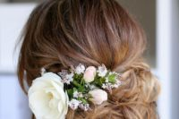 17 messy wedding updo with a big white bloom and some smaller ones