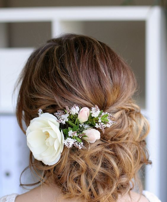 messy wedding updo with a big white bloom and some smaller ones