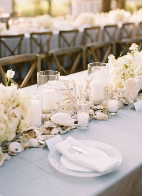 light blue tablecloth with a shell and coral table runner
