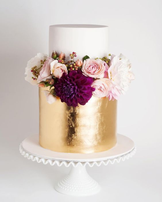 Picture Of white and gold wedding cake topped with fresh blooms