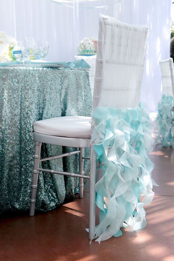 aqua-colored sequin tablecloth and ruffled aqua chair covers