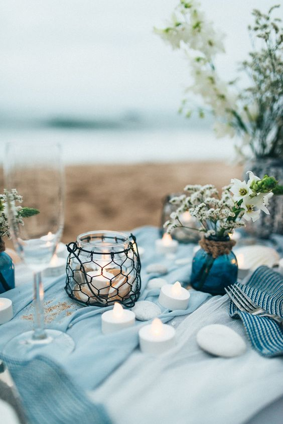 ocean blue weding table with candles and simple flowers