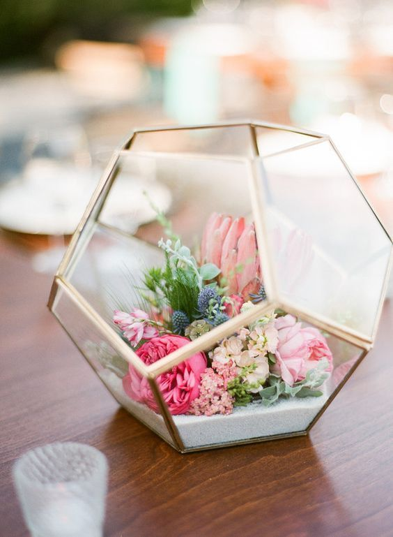 wedding centerpiece of a terrarium with bold florals