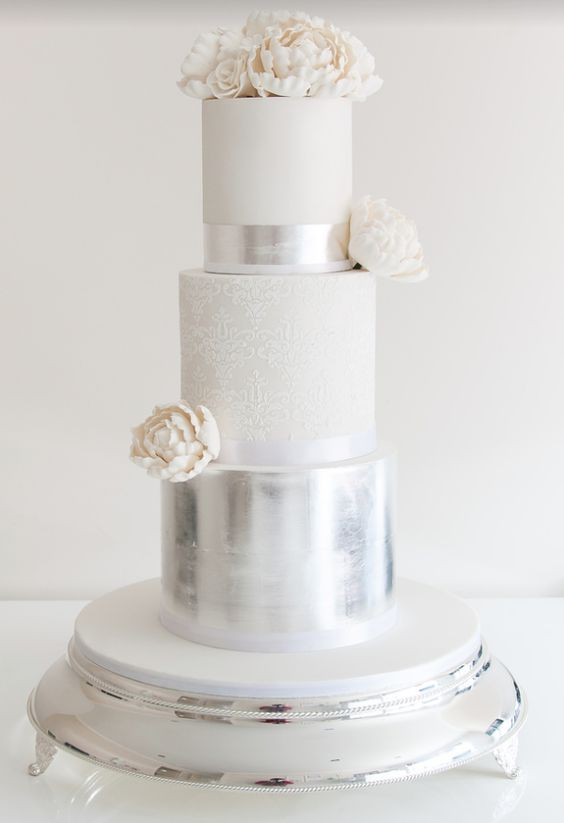 white, lace and silver wedidng cake with white flowers