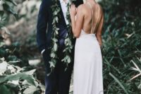 23 a black suit with a white shirt and a greenery garland